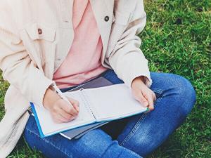 草むらに座ってノートに何かを書いているイメージ画像