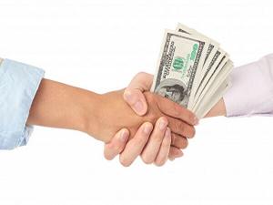 お金をやり取りして握手しているイメージ画像